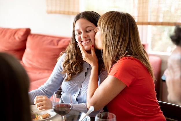 Mãe beijando a filha enquanto almoça em família