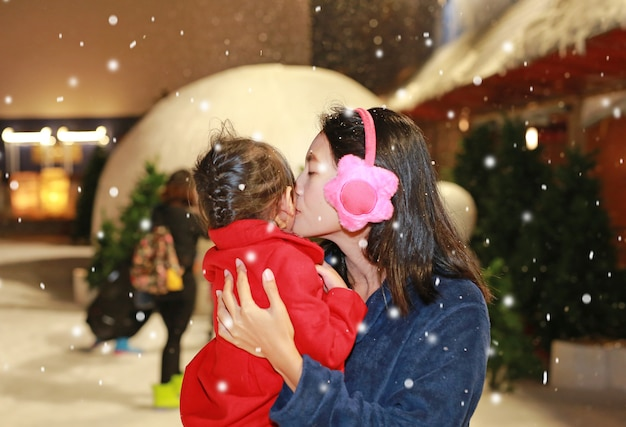 Mãe beijando a filha na neve, inverno.