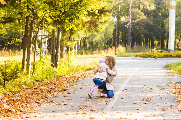 Mãe beijando a filha no parque mulher com criança na floresta de outono