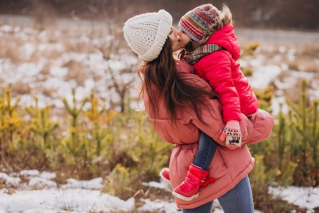 Mãe beijando a filha pequena em uma floresta de inverno