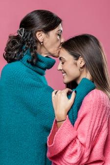 Mãe beijando garota na testa