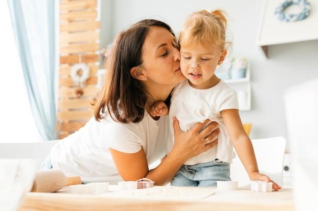 Mãe beijando menina bonitinha