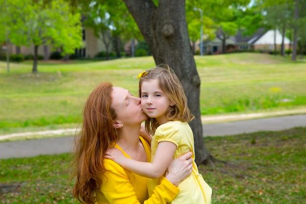 Mãe beijando sua filha loira no parque verde
