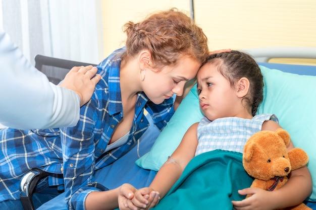 Mãe beijo, tranquilizando e discutindo sua filha. menina paciente triste no hospital do quarto.