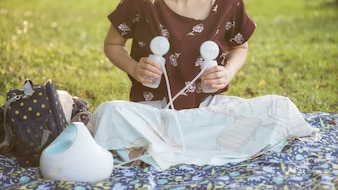 Mãe bomba leite materno no parque ao pôr do sol