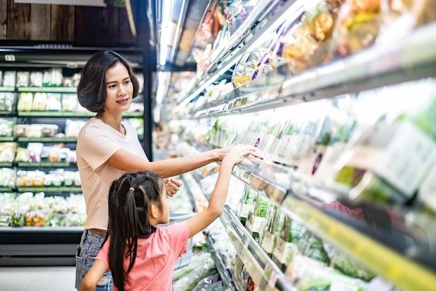 Mãe bonita asiática nova que guarda a cesta do mantimento com sua criança que anda no supermercado.