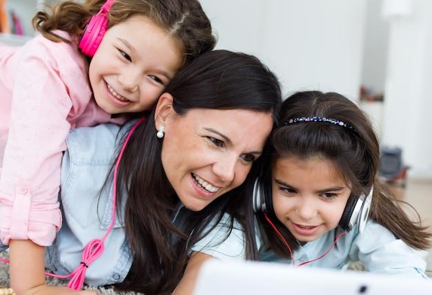 Mãe bonita com suas filhas que escutam a música em casa. Foto gratuita