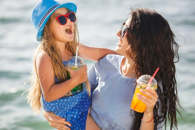Mãe bonita jovem e sua filha na praia se divertindo