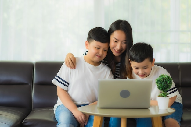 Mãe bonita jovem mulher asiática com seus dois filhos usando laptop no sofá