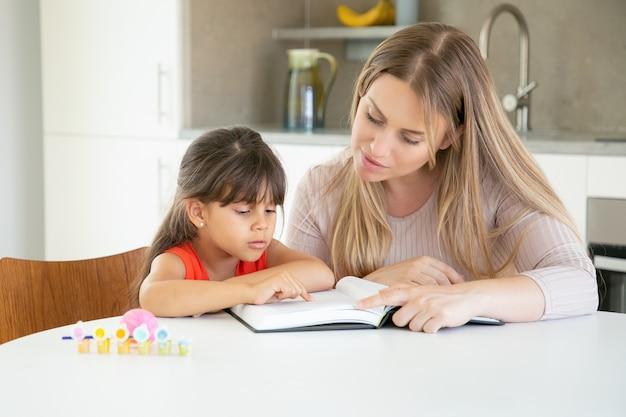 Mãe bonita lendo livro com a filha na cozinha.