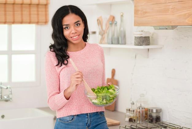 Mãe bonita que cozinha a salada em casa