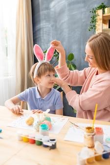 Mãe bonita sorridente ajustando a faixa das orelhas de coelho do filho enquanto eles se preparavam para a páscoa