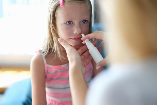 Mãe borrifando o nariz da menina com vasoconstritor em casa. tratamento da rinite em crianças conceito