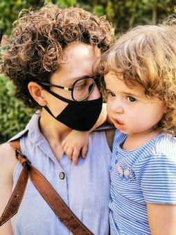 Mãe brasileira usando máscara cuidando da filha em quarentena.
