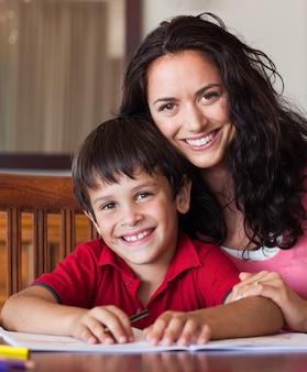 Mãe brilhante ajudando seu filho a fazer a lição de casa