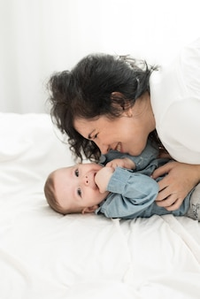 Mãe brinca com o bebê na cama. mãe faz cócegas no filho.