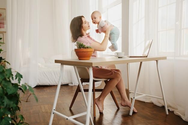 Mãe brinca com seu bebê. escritório em casa, freelance