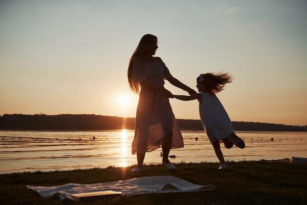 Mãe brinca com seu bebê nas férias perto do oceano, silhuetas ao pôr do sol