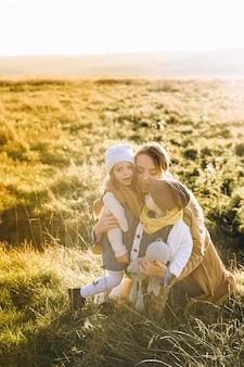 Mãe brinca com seus filhos na natureza ao pôr do sol