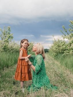 Mãe brinca com sua filha em lindos vestidos de primavera.
