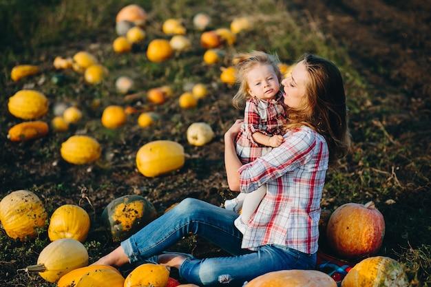 Mãe brincando com a filha em um campo com abóboras