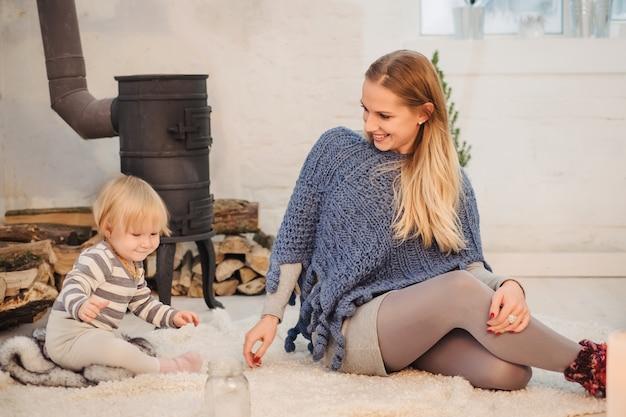 Mãe brincando com a menina perto da lareira retrô no chão