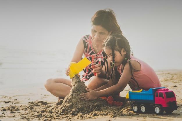 Mãe brincando com as crianças na praia com alegria
