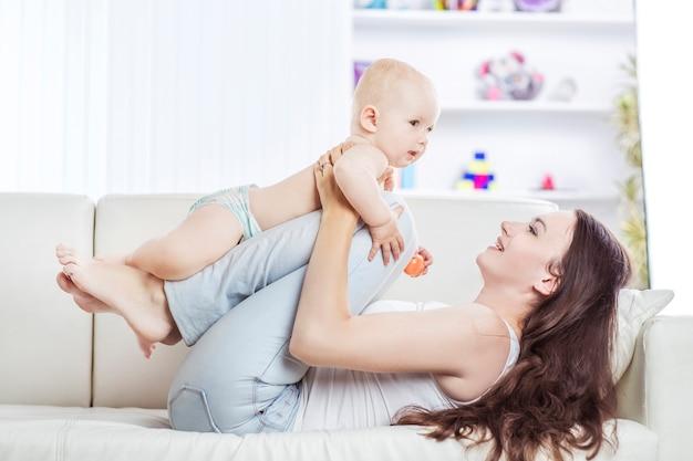 Mãe brincando com bebê de um ano no quarto das crianças