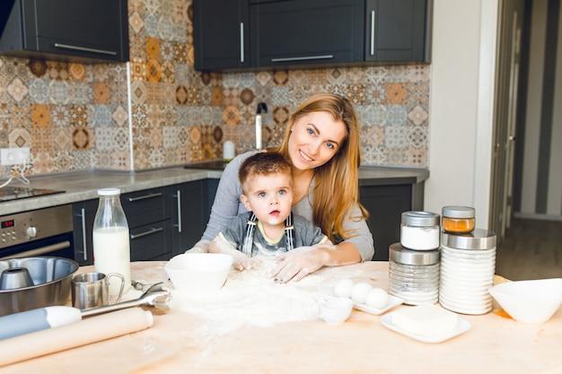 Mãe brincando com criança na cozinha. a cozinha é feita em cores escuras e estilo rústico.