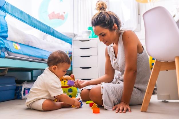 Mãe brincando com seu filho brincando sentado no chão