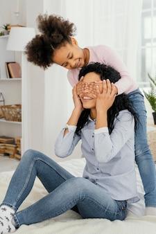 Mãe brincando com sua filha sorridente em casa
