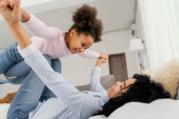 Mãe brincando com sua filha sorridente na cama em casa