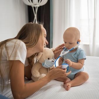 Mãe brincando com uma criança com um ursinho de pelúcia usando máscara médica