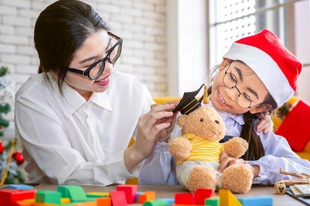 Mãe brincar com a filha com ursinho de pelúcia no feriado de natal.