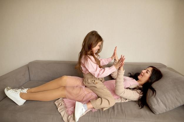 Mãe brincar com a filha no jogo de crianças. infância feliz. passem um tempo juntos em casa