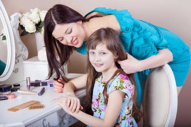 Mãe cabeleireiro sua linda filha pré-adolescente em casa.