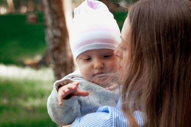 Mãe caminha com o bebê no parque. o bebê em seus braços. primavera.