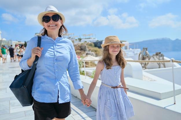 Mãe caminhando com a filha e a criança segurando a mão na vila turística de oia ilha de santorini