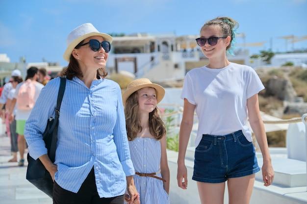 Mãe caminhando com duas filhas de mãos dadas na famosa vila turística de oia, na ilha de santorini