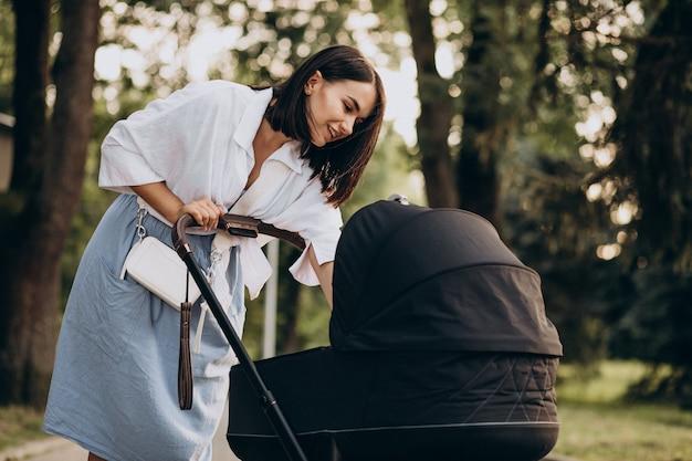 Mãe caminhando com sua filha bebê no parque