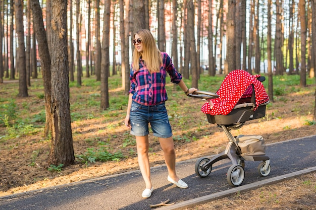 Mãe caminhando enquanto empurra um carrinho de bebê no parque.
