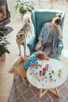 Mãe cansada e criança com autismo pintando aquarela juntas em