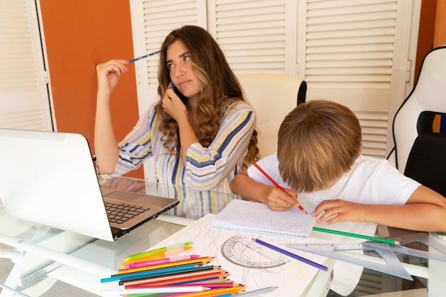 Mãe cansada, mãe sentada à mesa com o filho no colo, mãe tranquila usando um computador moderno, trabalho de casa em tempo de quarentena, pandemia de coronavírus, estilo de vida, paternidade, educação