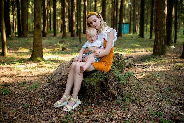 Mãe cansada posando com seu filho engraçado na floresta