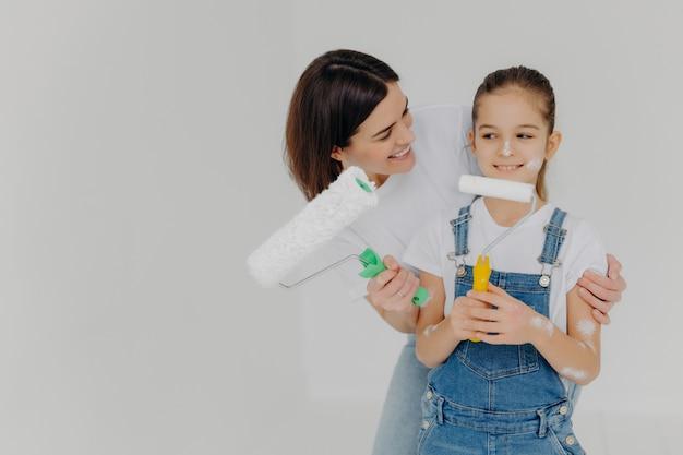 Mãe carinhosa abraça filha pequena com amor, pintar paredes da casa nova juntos