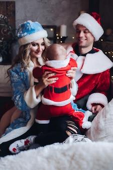Mãe carinhosa com casaco azul sentada ao lado do marido e do bebê, ambos vestidos com fantasias de papai noel. conceito de férias