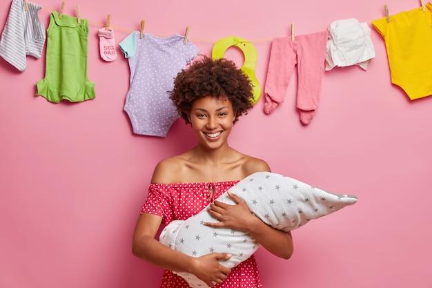 Mãe carinhosa e alegre segura seu filho pequeno de dois meses enrolado em um cobertor, brinca com o bebê, sendo uma jovem mãe responsável, aproveita os momentos da maternidade, encosta na corda com roupas infantis