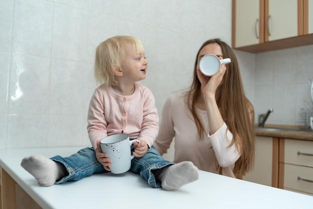 Mãe carinhosa e feliz e uma garota de cabelos louros bebem leite na cozinha.