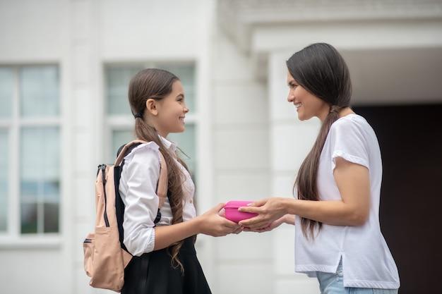 Mãe carinhosa e sorridente dando lancheira de colegial para a filha com lanche em pé e se despedindo perto da escola