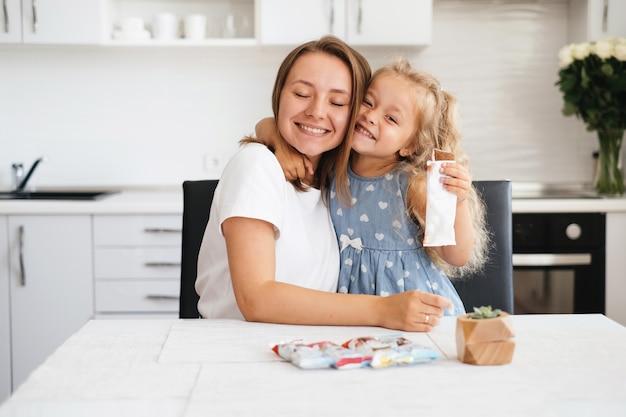 Mãe carinhosa e sua filha comendo um biscoito em casa